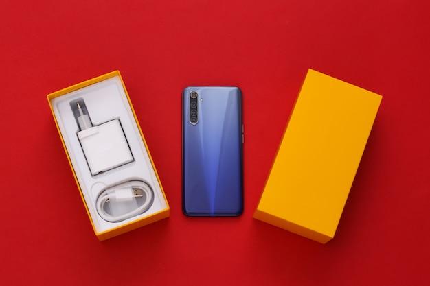 Novo smartphone moderno na caixa de embalagem em vermelho. minimalismo.