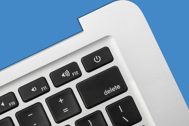Novo teclado prateado do laptop close-up sobre o fundo azul. espaço livre para texto