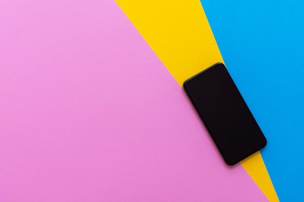 Novo telefone preto moderno com fundo colorido, disposição plana, espaço de cópia