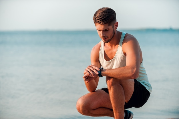 Novo tempo. homem jovem e musculoso confiante, verificando as horas em seus relógios enquanto está sentado à beira-mar