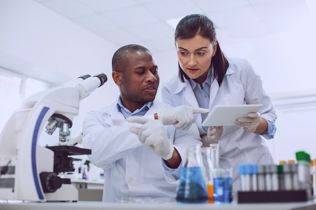 Novo teste. pesquisador qualificado e concentrado vestindo um uniforme e fazendo um teste
