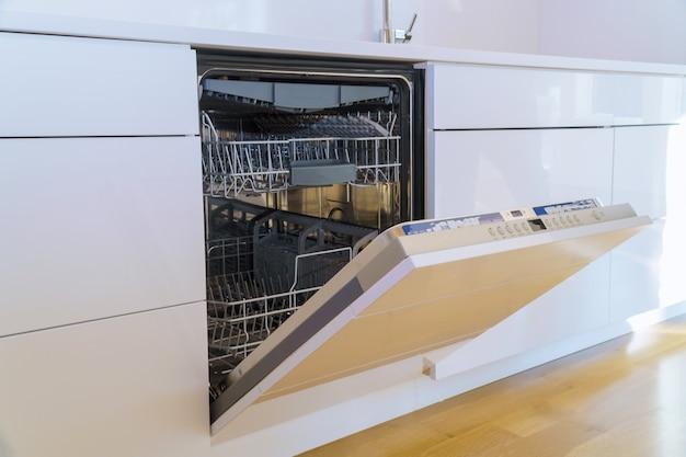 Novos aparelhos instalados na máquina de lavar louça na cozinha com armários de cozinha domésticos modernos