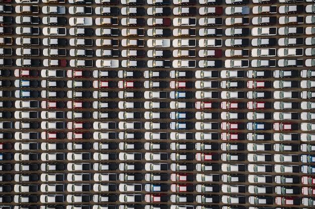 Novos carros alinhados no estacionamento para distribuição internacional para venda de negócios por grande corgo container transporte marítimo aberto