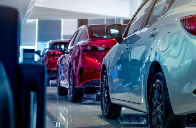 Novos carros vermelhos e brancos de luxo estacionados no moderno showroom