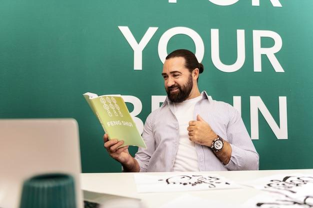 Novos detalhes homem barbudo de cabelos escuros vestindo uma camiseta branca e se sentindo animado ao ler um livro sobre feng shui