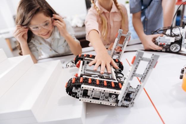 Novos dispositivos de jogo. alunos otimistas e curiosos encantados sentados na escola brincando com robôs cibernéticos enquanto têm aulas de ciências