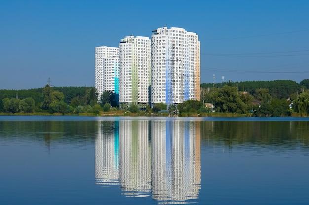 Novos edifícios altos, prédios de apartamentos perto do lago.