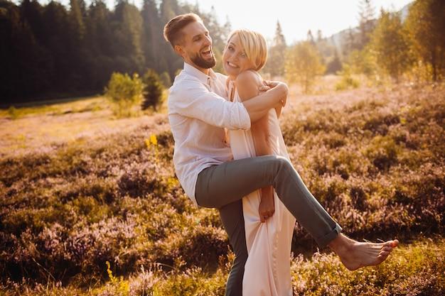 Novos noivos parecem engraçados posando no campo