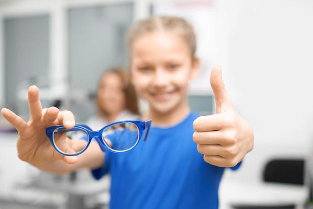 Novos óculos nas mãos da criança na loja de óptica