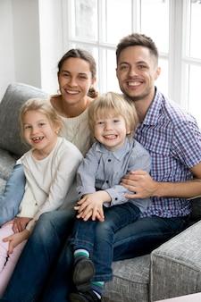 Novos pais felizes para dois filhos adotivos, retrato vertical da família