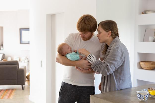Novos pais preocupados segurando e balançando bebê chorando