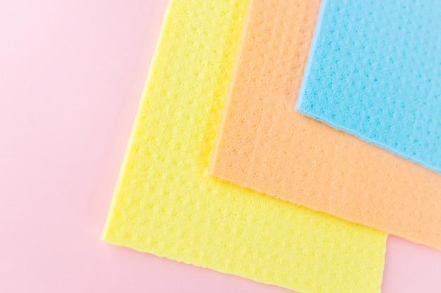 Novos panos para limpeza a úmido. trapos azuis, amarelos e laranja em rosa.