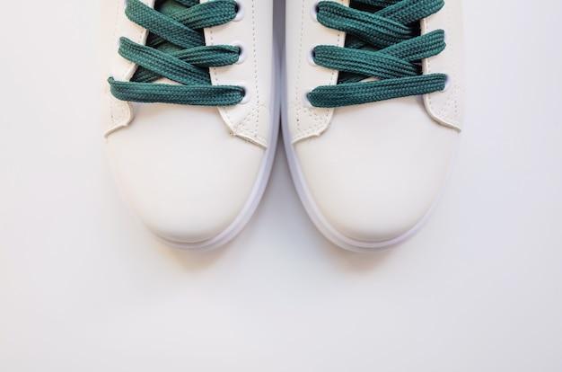 Novos tênis brancos com atacadores verdes sobre fundo branco