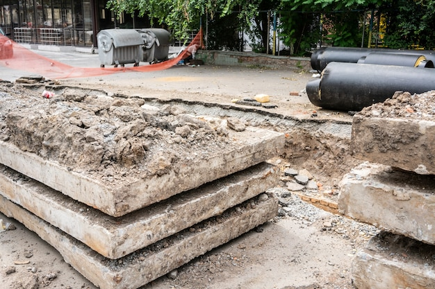 Novos tubos de água pretos isolados e lajes de concreto na estrada da cidade em dia de verão. conceito de infraestrutura de esgoto urbano, modernização e reconstrução de sistema subterrâneo.