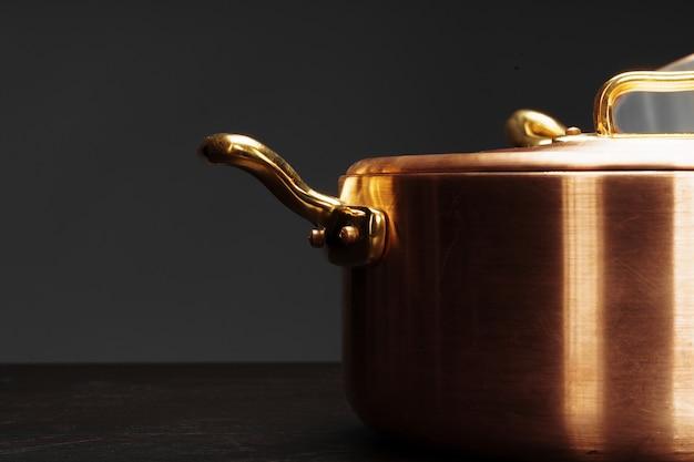 Novos utensílios de cobre para cozinhar sobre fundo escuro