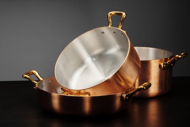 Novos utensílios de cobre para cozinhar sobre o escuro
