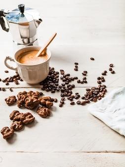 Noz de chocolate; grãos de café torrados e café expresso na mesa de madeira