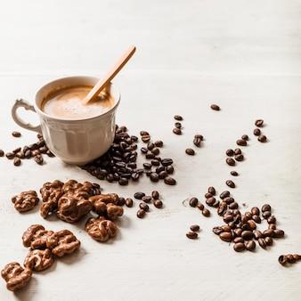 Noz de chocolate; grãos de café torrados e xícara de café sobre fundo de madeira