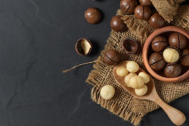 Noz de macadâmia torrada a seco em colher de madeira e em fundo preto,