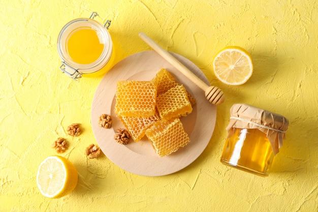 Noz, favos de mel, potes com mel, concha e limão sobre fundo amarelo, vista superior