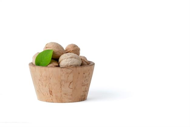Noz. nozes, frutas de diferentes variedades mentem em pires de madeira e cestas em um fundo branco e isolado. nas proximidades, há folhas verdes e frutos de nozes verdes.