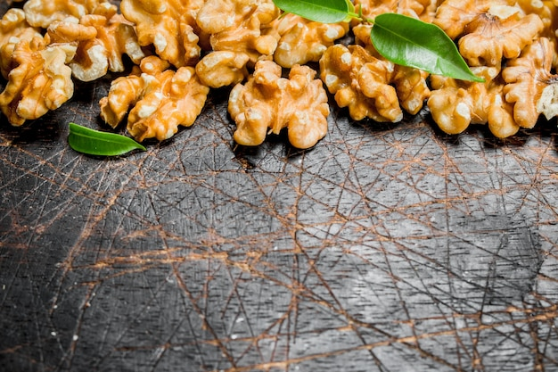 Noz sem casca com folhas verdes. sobre um fundo de madeira.