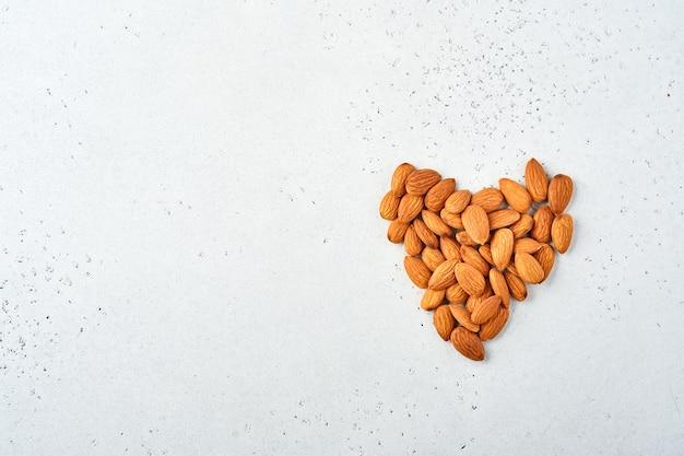 Nozes amêndoas dispostas em forma de um coração em fundo branco. lanche com comida vegana sem açúcar.