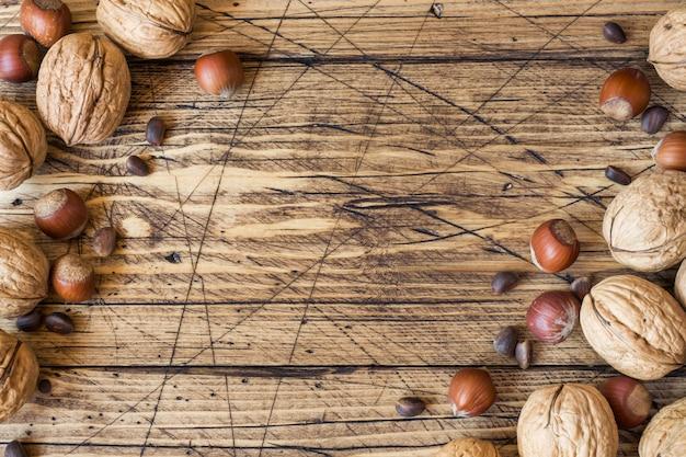 Nozes, avelã e cedro em uma superfície escura de madeira velha.
