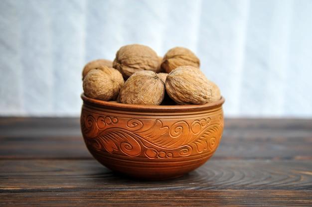 Nozes com casca em cerâmica sobre uma mesa de madeira