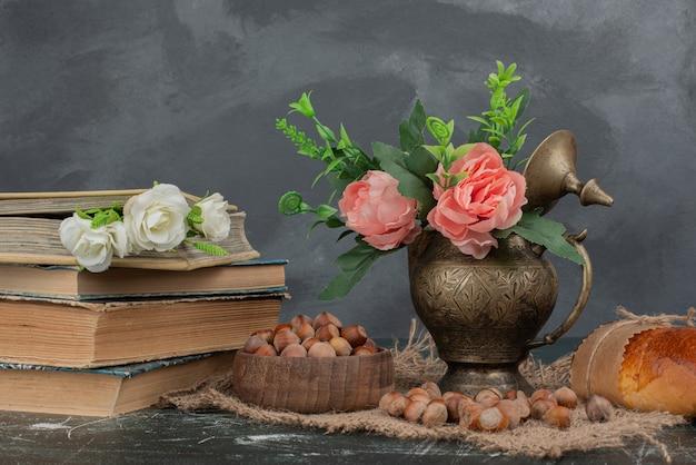 Nozes com livros e vaso de flores na mesa de mármore.