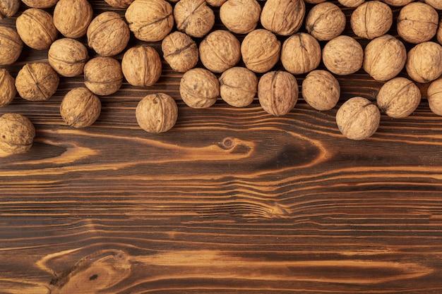 Nozes de casca dura na superfície de madeira com espaço de cópia