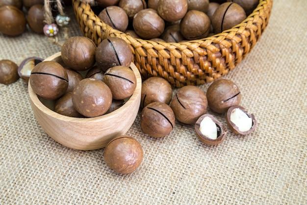 Nozes de macadâmia com e sem casca em mesa de madeira vintage