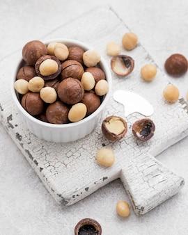Nozes de macadâmia dentro de rolos de chocolate na tábua de corte