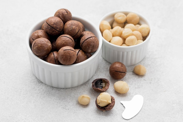 Nozes de macadâmia e chocolate em tigelas brancas