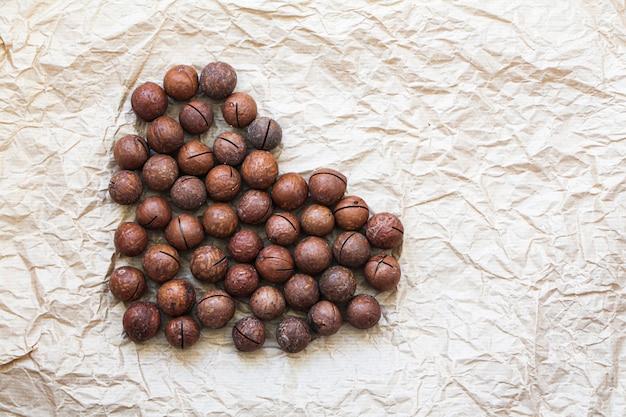 Nozes de macadâmia em forma de coração. conceito de comida saudável orgânica
