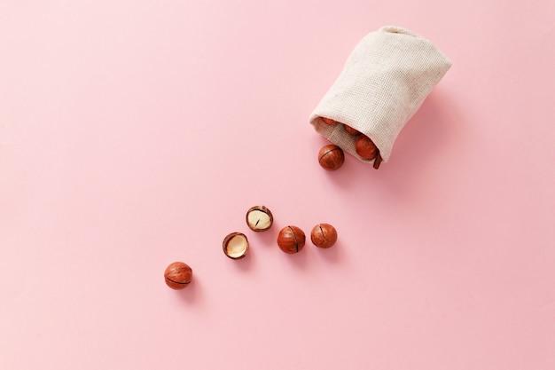 Nozes de macadâmia em um saco em um fundo rosa