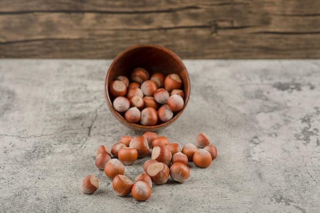 Nozes de macadâmia saudáveis com casca em um fundo de pedra.