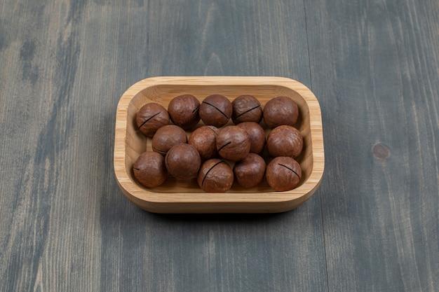 Nozes de macadâmia saudáveis em uma placa de madeira