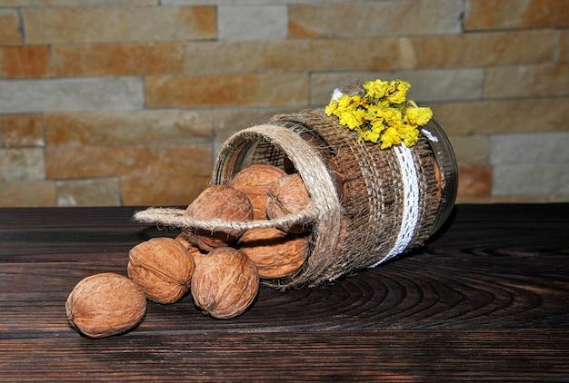 Nozes descascadas e descascadas em uma panela em forma de cesto e em uma panela de barro sobre uma mesa de madeira