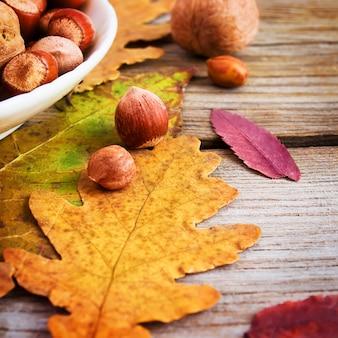 Nozes e folhas de outono brilhantes na madeira