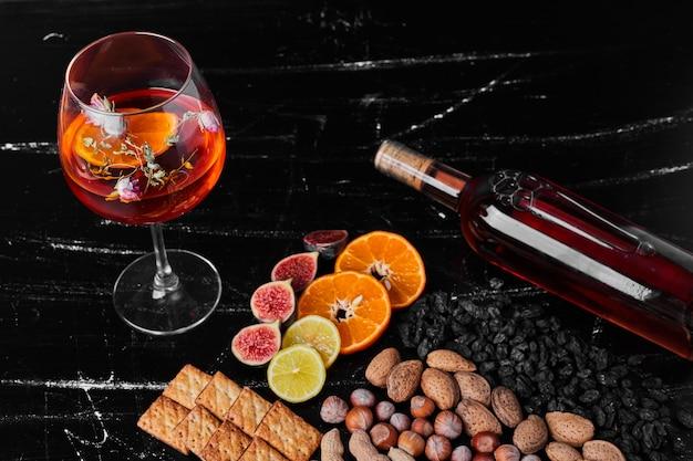 Nozes e frutas em fundo preto com um copo de bebida.
