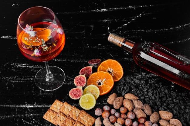 Nozes e frutas em fundo preto com vinho.