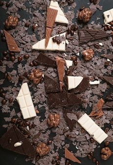 Nozes e grãos de café em pedaços de barra de chocolate