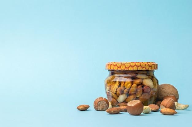 Nozes e um pequeno frasco com mel e nozes em um fundo azul. um remédio nutritivo natural.