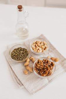 Nozes e vinagre em uma toalha de linho sobre uma mesa branca. nozes, castanhas de caju e sementes de abóbora para uma nutrição adequada. alimentos saudáveis e nutrientes para o cérebro e o corpo