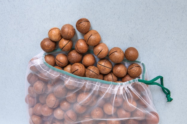 Nozes em embalagens ecológicas. sacos reutilizáveis para legumes e frutas. compras na loja. embalagem ecológica. cuidando da terra.