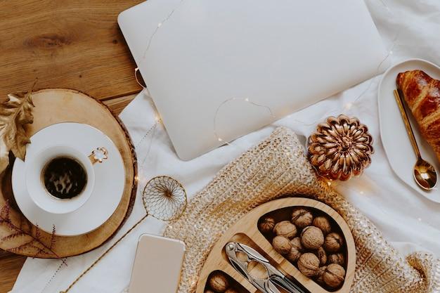 Nozes em uma caixa de madeira servidas com uma xícara de café ao lado de um laptop