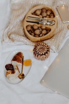 Nozes em uma caixa de madeira, um laptop e um prato de croissant em uma cama branca