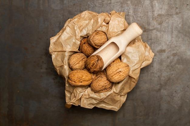 Nozes em uma tigela com um papel amassado e uma concha de madeira