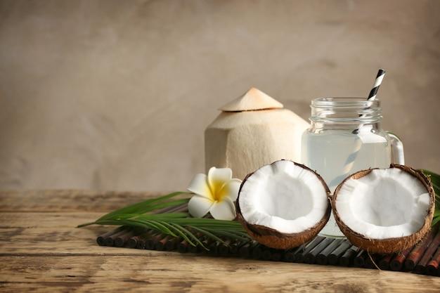 Nozes frescas e frasco de vidro com água de coco na esteira de bambu